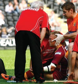 Huddersfield's Luke Robinson receives treatment on the field against Hull FC at the start of July